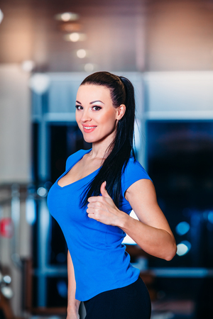 losing control: Happy smiling woman on the scales at the gym Stock Photo