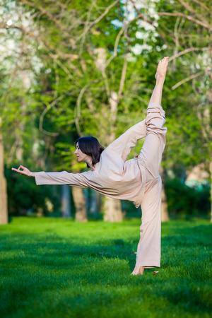 utthita: Yoga utthita trikonasana triangle pose by woman in white costume on green grass in the park around pine trees Stock Photo