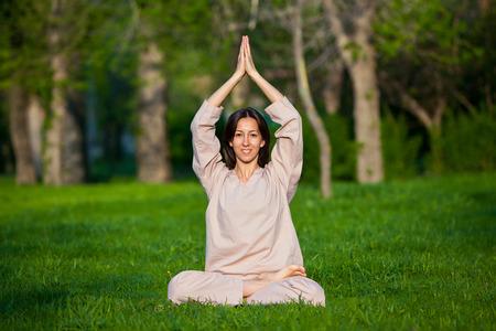 trikonasana: Yoga utthita trikonasana triangle pose by woman in white costume on green grass in the park around pine trees Stock Photo