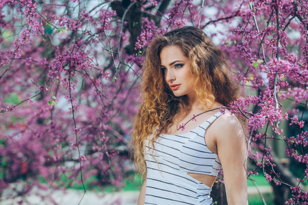 frizz: portrait of young lovely woman in spring flowers