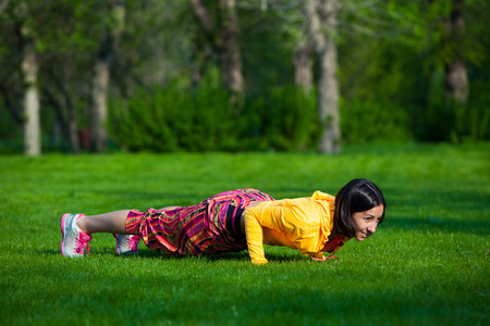 girl working out: Push ups or press ups exercise by young woman. Girl working out on grass crossfit strength training in the glow of the morning sun Stock Photo