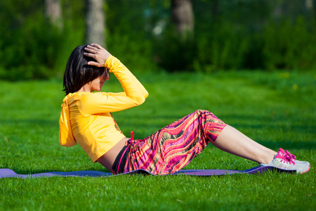 girl working out: Push ups or press ups exercise by young woman. Girl working out on grass crossfit strength training in the glow of the morning sun against a white sky with copyspace. Mixed race Asian Caucasian model. Stock Photo