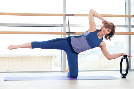 saxy: fitness, sport, training and lifestyle concept -  girl doing pilates with ring