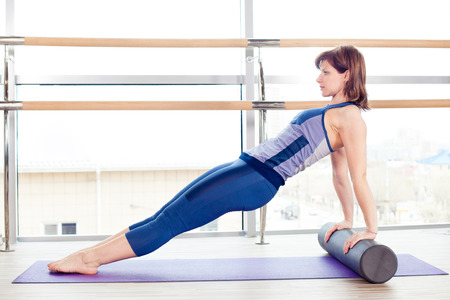 roller: fitness, sport, training and lifestyle concept -  woman doing pilates on the floor with foam roller Stock Photo