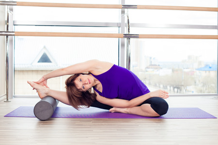 saxy: fitness, sport, training and lifestyle concept -  woman doing pilates on the floor with foam roller Stock Photo