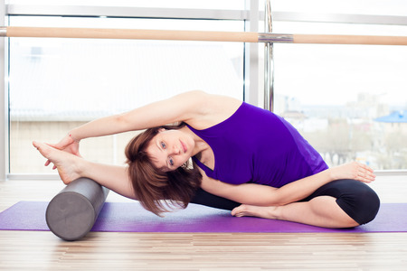 yoga class: fitness, sport, training and lifestyle concept -  woman doing pilates on the floor with foam roller Stock Photo