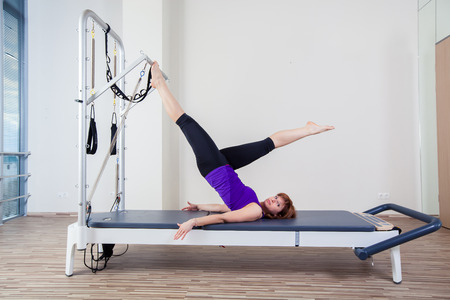 pilates woman: gym woman pilate instructor stretching in reformer bed