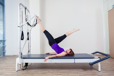 reformer: gym woman pilate instructor stretching in reformer bed