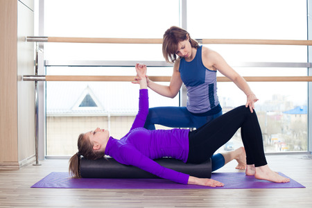 personal trainer: Aerobics Pilates personal trainer helping women group in a gym class