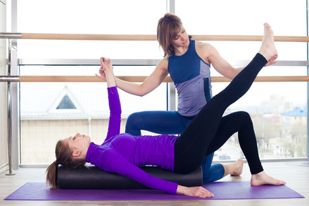 limber: Aerobics Pilates personal trainer helping women group in a gym class