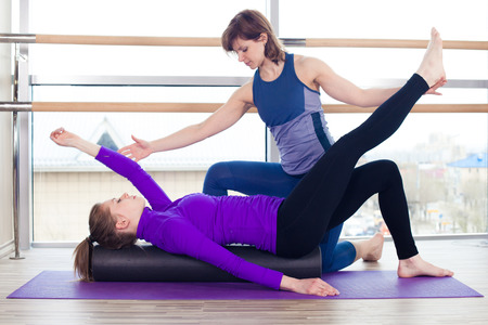 pilates studio: Aerobics Pilates personal trainer helping women group in a gym class