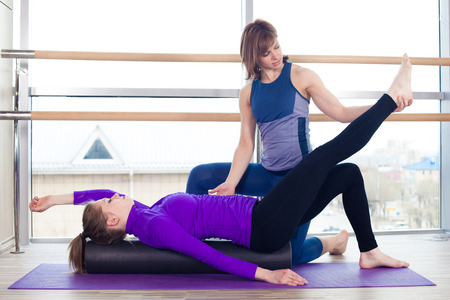 laying abs exercise: Aerobics Pilates personal trainer helping women group in a gym class