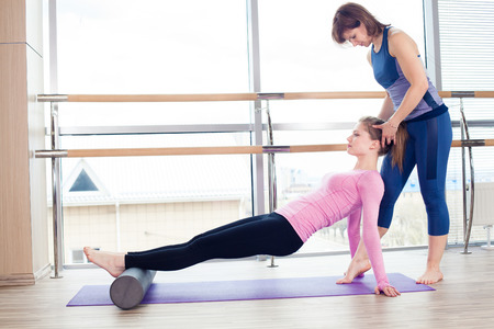 pilates man: Aerobics Pilates personal trainer helping women group in a gym class