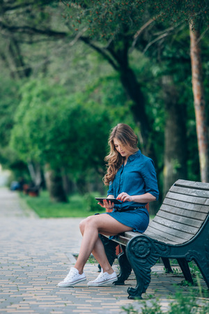 Side view of a young woman using a tablet computer on a park bench photo