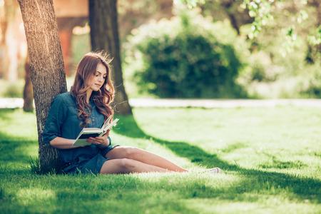 personas leyendo: Niña leyendo un libro en el parque, mujer, verde Foto de archivo