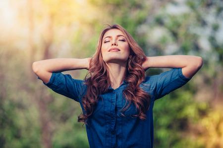無料幸せな女を楽しむ自然。屋外の美しさの少女。自由の概念。美少女日木漏れ日と空の上。楽しみ。 写真素材