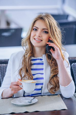 Young woman at cafe drinks coffee and talking on the mobile phone photo