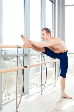barre: in the hall man doing stretching near Barre.