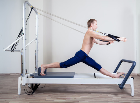 hang body: Pilates reformer workout exercises man at gym indoor Stock Photo
