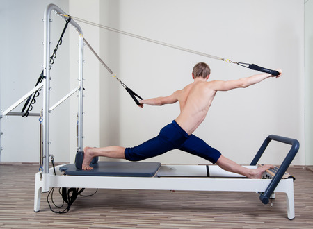 pilates man: Pilates reformer workout exercises man at gym indoor Stock Photo