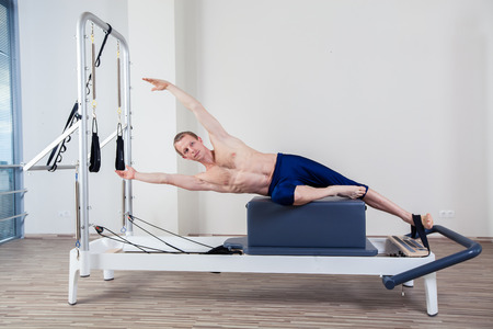 Pilates reformer workout exercises man at gym indoor Stock fotó