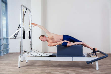 Pilates reformer workout exercises man at gym indoor photo