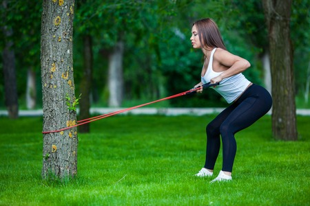 expander: fitness, sport, people and lifestyle concept - smiling woman doing exercises with expander in outdoors, park