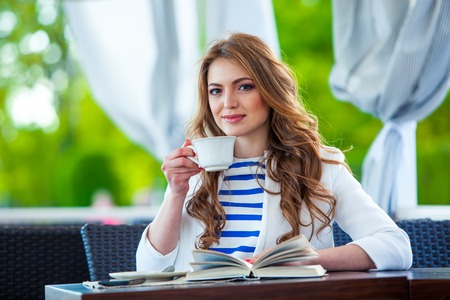 cute girl: beautiful young girl in outdoor cafe reading a book and drinking coffee. phone. student. business woman