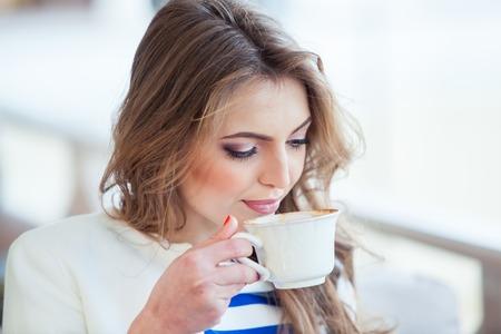 Bella ragazza in bar all'aperto a leggere un libro e bere il caffè. telefono. studente. donna d'affari Archivio Fotografico - 40614774