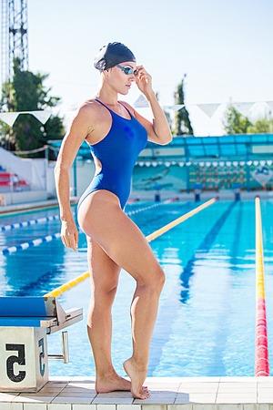 birretes: Retrato de un nadador femenino, que llevaba una gorra de natación y gafas y se prepara para saltar a la piscina. Mujer deportiva.