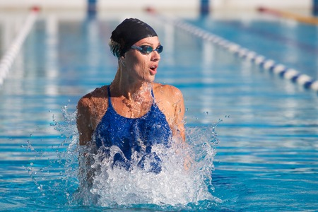 professional swimmer, water splashing, goggles and swimming cap Фото со стока