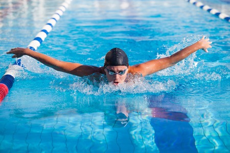 front raise: Butterfly swimmer in cap and glasses in the pool