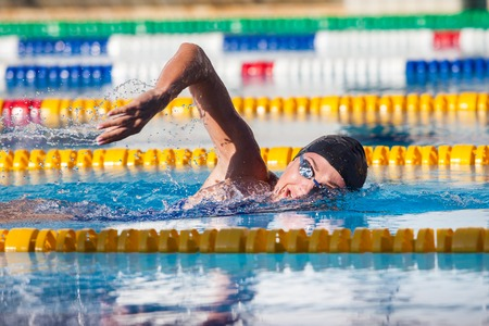 freestyle: Man swims crawl in the pool, goggles, hat.