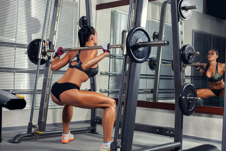 crouches: beautiful sports fitness girl with a barbell in the gym, crouches