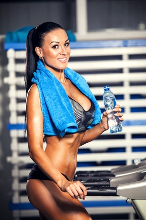 Smiling athletic woman drinking water on a treadmill Archivio Fotografico