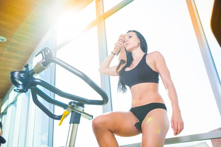 weary: Beautiful woman at the gym on bike, cycle, sunny gym, general plan, weary