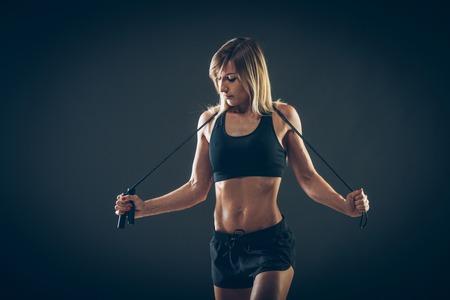rope background: Sport, activity. Cute woman with skipping rope. Muscular woman  black background.