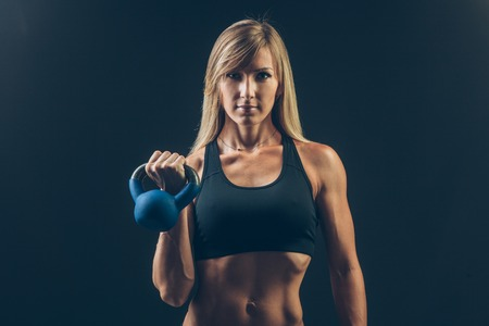 Fitness woman exercising crossfit holding kettlebell strength training biceps. Beautiful sweaty fitness instructor on blackoard background looking intense at camera. Asian Caucasian female model. Standard-Bild