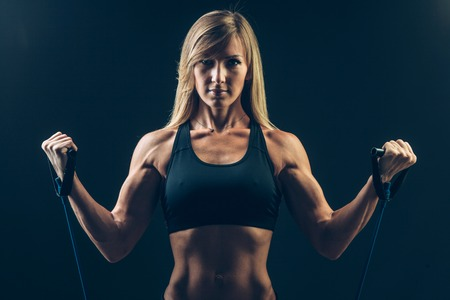 Athletic young woman working on biceps with expander Stock Photo