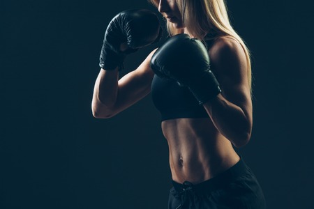 female boxer: beautiful woman with the red boxing gloves,black background
