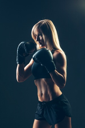 girl action: beautiful woman with the red boxing gloves,black background