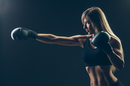 girl punch: beautiful woman with the red boxing gloves,black background