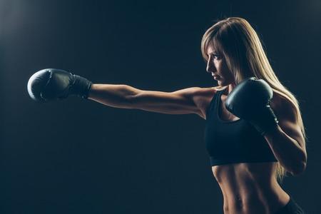 patada: mujer hermosa con los guantes de boxeo rojos, fondo negro