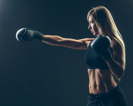 sexy young girl: beautiful woman with the red boxing gloves,black background