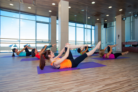 women sport: fitness, sport, training and lifestyle concept - group of smiling women stretching in gym.