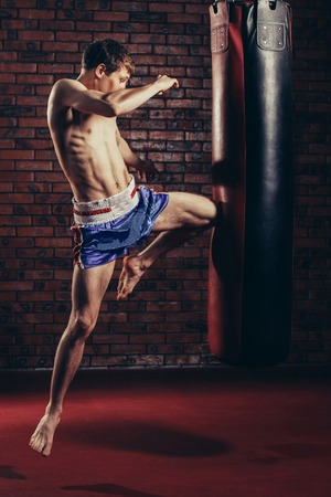 muscular handsome fighter giving a forceful forward kick during a practise round with a boxing bag, kickboxing.