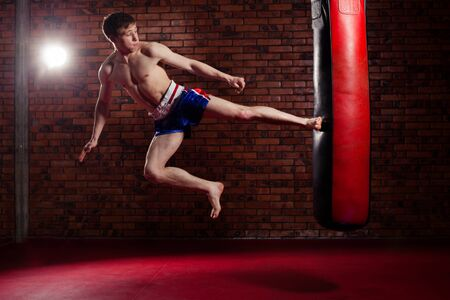 forceful: muscular handsome fighter giving a forceful forward kick during a practise round with a boxing bag, kickboxing.
