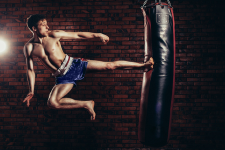 kickboxing: muscular handsome fighter giving a forceful forward kick during a practise round with a boxing bag, kickboxing.