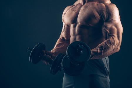 muscle: Hombre del músculo haciendo flexiones de bíceps. Hombre del músculo haciendo flexiones de bíceps Foto de archivo