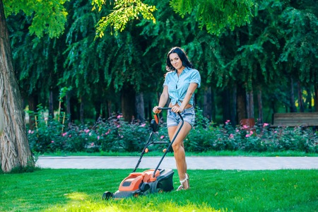 woman gardening: Woman mowing lawn in residential back garden on sunny day.